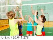 Купить «Teenagers playing volleyball in school gymnasium», фото № 26641278, снято 16 апреля 2017 г. (c) Сергей Новиков / Фотобанк Лори