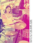 Купить «Adult girl selecting drums and accessories», фото № 26645326, снято 13 ноября 2018 г. (c) Яков Филимонов / Фотобанк Лори