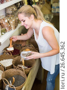 Купить «young woman picking dried beans in store», фото № 26645362, снято 15 ноября 2018 г. (c) Яков Филимонов / Фотобанк Лори