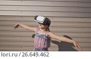 Купить «Happy amazed little girl wearing virtual reality goggles watching movies or playing video games. Cheerful surprised child looking in VR glasses. On a striped background.», видеоролик № 26649462, снято 10 июля 2017 г. (c) Mikhail Davidovich / Фотобанк Лори