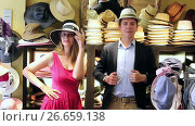 smiling adult woman and man trying on fashion hats in the shopping mall. Стоковое видео, видеограф Яков Филимонов / Фотобанк Лори