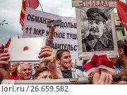 Участник митинга КПРФ держит портрет Иосифа Сталина на площади Революции в центре города Москвы, Россия 15 июля 2017. Редакционное фото, фотограф Николай Винокуров / Фотобанк Лори