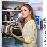 Купить «Hungry female standing near fridge with pan of food», фото № 26659886, снято 4 декабря 2019 г. (c) Яков Филимонов / Фотобанк Лори