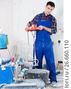 Купить «Builder mixing plaster in bucket with electric mixer», фото № 26660110, снято 21 мая 2017 г. (c) Яков Филимонов / Фотобанк Лори
