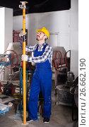 Купить «working man practicing his skills erect trestle at workshop», фото № 26662190, снято 17 января 2017 г. (c) Яков Филимонов / Фотобанк Лори