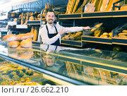 Купить «Man shows a variety of loaves of bread», фото № 26662210, снято 26 января 2017 г. (c) Яков Филимонов / Фотобанк Лори