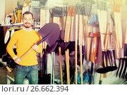 Купить «Happy guy deciding on best shovel», фото № 26662394, снято 2 марта 2017 г. (c) Яков Филимонов / Фотобанк Лори