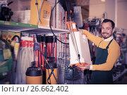 Купить «Ordinary guy deciding on best garden sprayer», фото № 26662402, снято 2 марта 2017 г. (c) Яков Филимонов / Фотобанк Лори