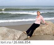 Купить «Женщина средних лет сидит на валуне. Берег Балтийского моря», фото № 26666854, снято 21 августа 2011 г. (c) Ирина Борсученко / Фотобанк Лори