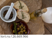 Купить «Directly above shot of olives with oil bottle and bread by spices in mortar pestle on crumbled paper», фото № 26669966, снято 15 февраля 2017 г. (c) Wavebreak Media / Фотобанк Лори