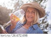Купить «Woman looking at glass of wine in olives farm», фото № 26672698, снято 22 марта 2017 г. (c) Wavebreak Media / Фотобанк Лори