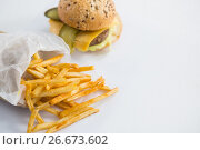 Купить «High angle view of French fries by burger», фото № 26673602, снято 13 января 2017 г. (c) Wavebreak Media / Фотобанк Лори