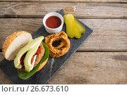 Купить «High angle veiw onion rings with burger on slate», фото № 26673610, снято 13 января 2017 г. (c) Wavebreak Media / Фотобанк Лори