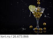 Купить «Olives splashing in to a cocktail martini with lime on table», фото № 26673866, снято 15 февраля 2017 г. (c) Wavebreak Media / Фотобанк Лори
