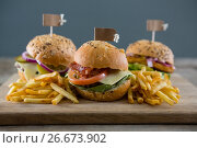 Купить «Close up of burgers with french fries served on cutting board», фото № 26673902, снято 13 января 2017 г. (c) Wavebreak Media / Фотобанк Лори