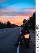 Купить «Мотоциклист стоит на пустой вечерней трассе с красивым закатом на горизонте», фото № 26676486, снято 9 июля 2017 г. (c) Кекяляйнен Андрей / Фотобанк Лори