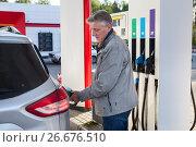 Купить «Мужчина заправляет свой автомобиль», фото № 26676510, снято 10 июля 2017 г. (c) Кекяляйнен Андрей / Фотобанк Лори