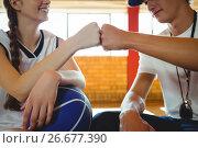 Купить «Close-up of female basketball player doing fist bump with male coach», фото № 26677390, снято 18 февраля 2017 г. (c) Wavebreak Media / Фотобанк Лори