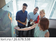 Купить «High angle view of businesswoman explaining to colleagues over whiteboard», фото № 26678538, снято 5 марта 2017 г. (c) Wavebreak Media / Фотобанк Лори