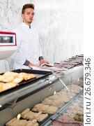 Купить «Seller in his grocery shop welcoming customers», фото № 26679346, снято 25 марта 2019 г. (c) Яков Филимонов / Фотобанк Лори