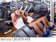 Купить «man and woman making sit ups together using machine in gym», фото № 26679478, снято 16 июля 2019 г. (c) Яков Филимонов / Фотобанк Лори