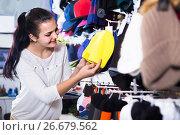 Купить «girl deciding on warm hat in sports store», фото № 26679562, снято 22 ноября 2016 г. (c) Яков Филимонов / Фотобанк Лори