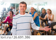 Купить «Elderly man on fitness cycle in fitness club», фото № 26691386, снято 21 мая 2019 г. (c) Яков Филимонов / Фотобанк Лори