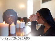 Купить «sad woman with funerary urn praying at church», фото № 26693690, снято 20 марта 2017 г. (c) Syda Productions / Фотобанк Лори