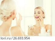 Купить «happy woman applying cream to face at bathroom», фото № 26693954, снято 13 февраля 2016 г. (c) Syda Productions / Фотобанк Лори