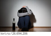 woman with bottle of alcohol crying at home. Стоковое фото, фотограф Syda Productions / Фотобанк Лори