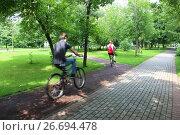Купить «Велосипедисты едут по велодорожке в благоустроенном московском парке», фото № 26694478, снято 16 июля 2017 г. (c) Елена Орлова / Фотобанк Лори
