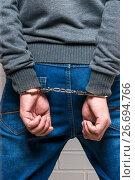 Купить «Behind the hand in handcuffs close-up, the criminal is caught!», фото № 26694766, снято 1 октября 2016 г. (c) Константин Лабунский / Фотобанк Лори