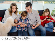 Купить «Family playing with their smartphones together at home», фото № 26695694, снято 23 декабря 2016 г. (c) Яков Филимонов / Фотобанк Лори