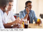 Купить «man calling on smartphone and drinking beer at bar», фото № 26700154, снято 2 мая 2017 г. (c) Syda Productions / Фотобанк Лори