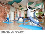 Купить «group of people doing yoga warrior pose at studio», фото № 26700394, снято 5 марта 2017 г. (c) Syda Productions / Фотобанк Лори