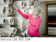 Купить «Laughing woman choosing interesting fabric», фото № 26707734, снято 15 февраля 2017 г. (c) Яков Филимонов / Фотобанк Лори