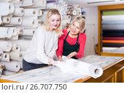 Купить «Shop assistant is showing fabrics to young customer», фото № 26707750, снято 15 февраля 2017 г. (c) Яков Филимонов / Фотобанк Лори