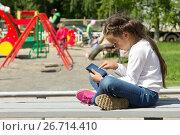 Купить «Девочка с планшетом в руках на фоне детской площадки», фото № 26714410, снято 30 июня 2017 г. (c) Лариса Капусткина / Фотобанк Лори