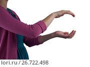 Купить «Teenage girl pretending to be hold invisible object», фото № 26722498, снято 24 января 2017 г. (c) Wavebreak Media / Фотобанк Лори