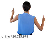 Rear view of businesswoman in sleeveless clothing pointing on interface. Стоковое фото, агентство Wavebreak Media / Фотобанк Лори