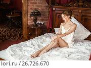 Купить «Красивая девушка сидит на постели», фото № 26726670, снято 6 апреля 2017 г. (c) katalinks / Фотобанк Лори