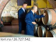 two busy men in uniforms taking notes in cellar with wine woods. Стоковое фото, фотограф Яков Филимонов / Фотобанк Лори