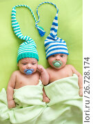 Купить «Twins infant brothers babies weared in striped hats tied by heart.», фото № 26728174, снято 27 сентября 2012 г. (c) Оксана Кузьмина / Фотобанк Лори