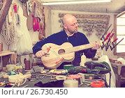 Купить «Guitar-maker at workshop», фото № 26730450, снято 28 января 2020 г. (c) Яков Филимонов / Фотобанк Лори
