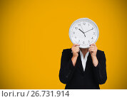 Купить «Woman holding clock in front of yellow background», фото № 26731914, снято 16 июня 2019 г. (c) Wavebreak Media / Фотобанк Лори