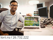 Купить «Man holding a computer with e-learning information in the screen», фото № 26732222, снято 22 июля 2019 г. (c) Wavebreak Media / Фотобанк Лори