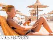 Sensuous slim woman applying suntan oil. Стоковое фото, фотограф Никита Буйда / Фотобанк Лори