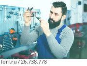 Купить «Adult is observing motorbike part for fixing», фото № 26738778, снято 25 сентября 2018 г. (c) Яков Филимонов / Фотобанк Лори