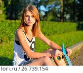 Купить «Молодая девушка с длинными волосами сидит на поребрике со скейтбордом в парке», фото № 26739154, снято 27 июля 2017 г. (c) Максим Мицун / Фотобанк Лори