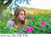 Купить «Молодая девушка сидит у шиповника в парке на закате», фото № 26739174, снято 27 июля 2017 г. (c) Максим Мицун / Фотобанк Лори
